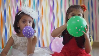 Pretty little girls blowing up balloons at the birthday party - Indian kids having fun at the party