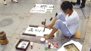 Amazing Chinese street artist paints calligraphy with feet - Zhuhai, China
