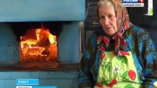 Бабушка печет в старинной печи Пласт