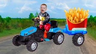 Малыш на синем тракторе с ковшом помогает загрузить Картофель