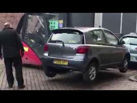 Workers solve parking problem by moving car with forklift truck