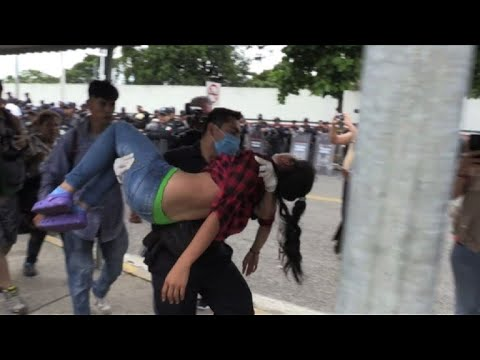 Mexican police carries migrants who fainted from border bridge