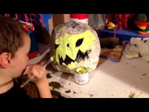 Painting halloween pumpkin jackolantern made of paper mache