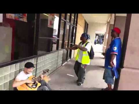 A Man Playing Guitar Is Joined By Two Strangers In An Impromptu Street Performance.