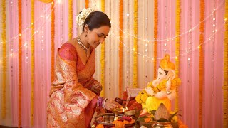 Indian young woman lighting up diya while praying - Ganesh festival puja. Colorful Festive Background
