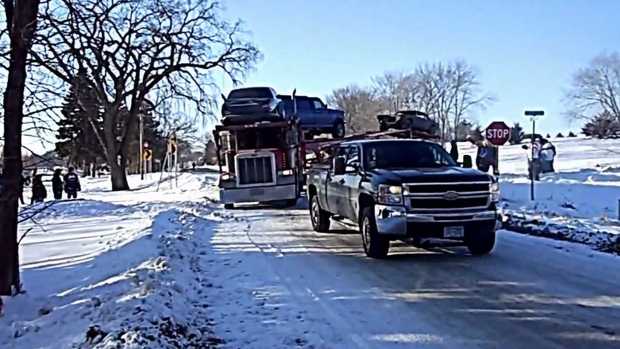 chevy silverado dmax pulling a jackknifed semi-trailer hauling cars out of a ditch