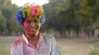 Funny Indian guy smeared in organic Gulal smiling at the camera - Holi festival, India