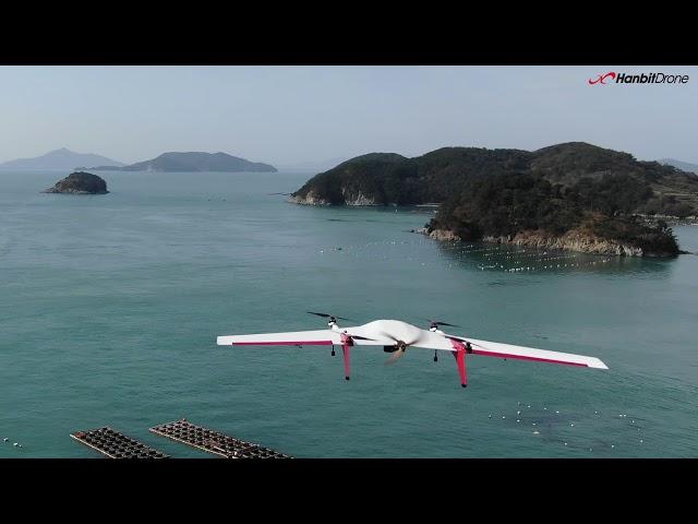 VTOL fixed-wing MILVUS flies over Korean national park shore.