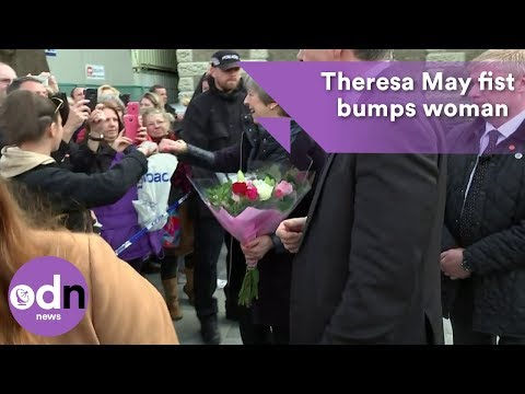 Theresa May shares a fist bump with a member of the public