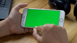 A woman enjoying music video and movie on her smartphone with green screen