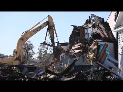 Heavy equipment demolishes remaining fire-damaged buildings