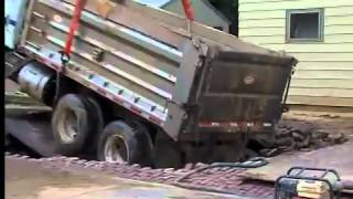 Dump truck falls in hole