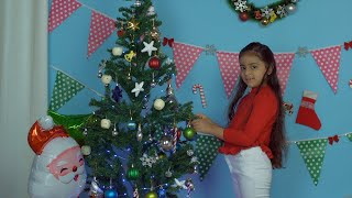Happy little girl hanging colorful balls and other beautiful items on a Christmas tree - festive scene
