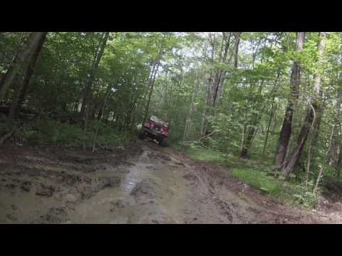 Jeep TJ on 37 inch pit bull rockers plows through salamander pit.  Unique view from rear