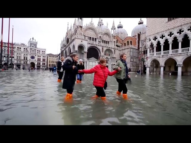 Woman's Luggage Floats Along Flooded Streets of Venice