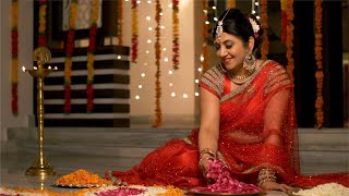 Diwali Festival - Traditional Indian house wife in red saree making flower rangoli