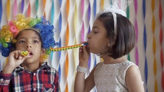 Adorable kids blowing blow out whistle at each other at a birthday party - Indian kids having fun