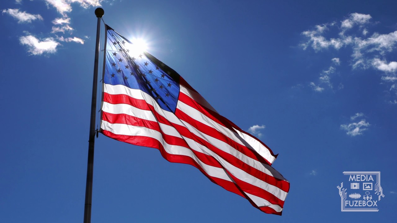 American Flag Waving Against A Blue Sky With Sun Glowing From Behind