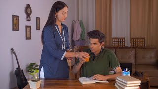 Young Indian teenager preparing for exams while caring mother offers juice - Concerned parents