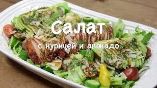Салат с курицей, авокадо, овощами и листьями салата.