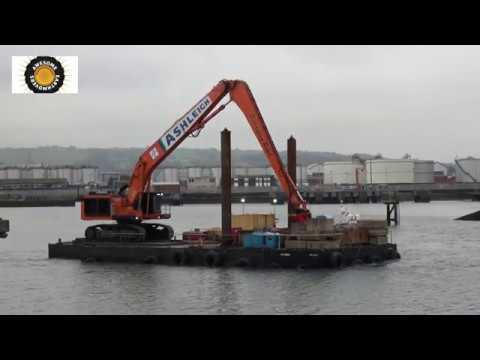 Hitachi EX1200 excavator pulling itself along on a barge.