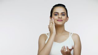 Young attractive girl applies skincare cream to her face for healthy skin - beauty concept