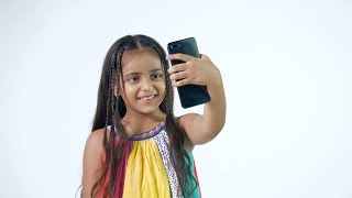 Young innocent kid busy doing a video call from her smartphone - modern technology