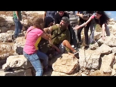 Palestinian women and children fight off Israeli soldier wit