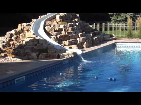 Custom built pool slide with rock surround