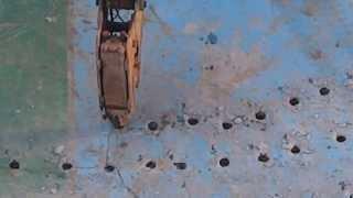 破碎機在舖面上打洞後,再以挖土機挖除舖面