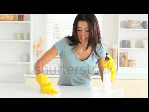 stock footage young woman cleaning her kitchen with yellow gloves