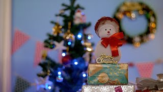 Bokeh shot of a cute toy snowman placed on a pile of Christmas presents at home