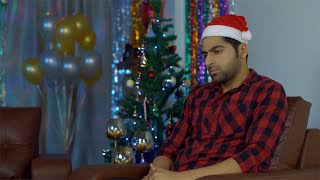 A young man in Santa hat is sitting alone on a couch during Christmas time in India