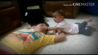 Cute baby trying to wake up his elder brother...