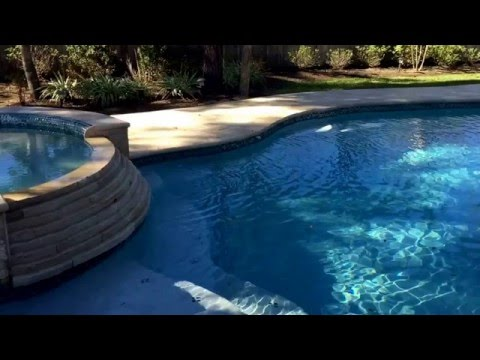 Free form travertine decking , stair step dam wall , custom spa with neck roll