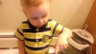 Liam plays with his tablet on the potty.