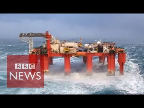 Huge waves crash against swaying North Sea oil rig