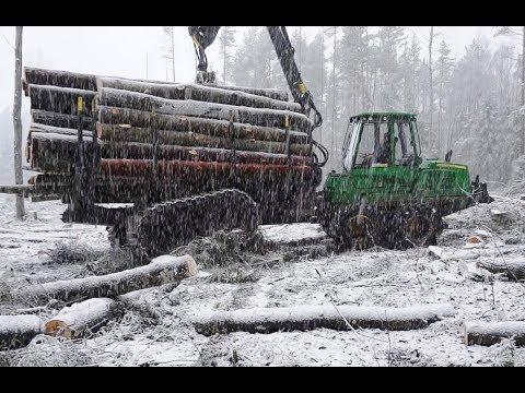 John Deere 1110E logging in snowy forest, big load, skilled operator