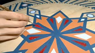 Moments of painting a mandala on a wooden table. Mandala Tales unique design