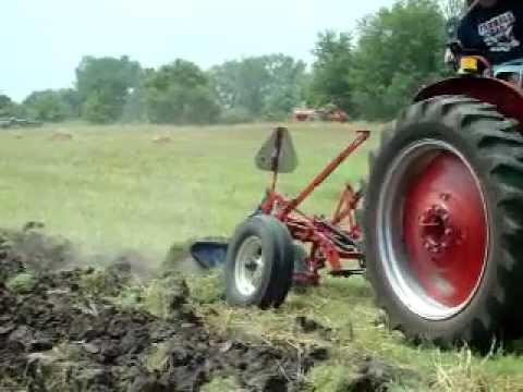 Farmall M Tractor Plowing a Field with a 2-Bottom Plow