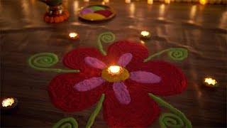 Tilt shot of beautiful burning Diyas decorated on a colorful rangoli on Diwali - the festival of lights
