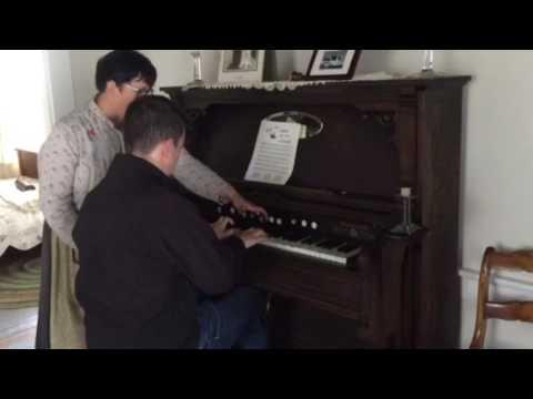 Xander playing pump organ