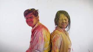Young teenagers sitting still while being covered in colorful powder - Holi festival
