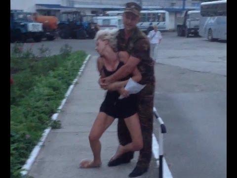 Охранник санатория ФСБ тащит по асфальту полудохлую девушку чтобы выкинуть её за ворота.