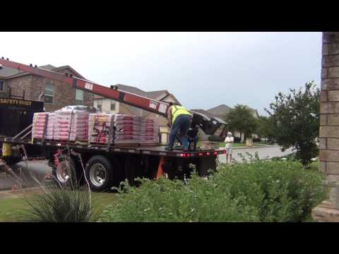 Loading New Shingles onto the Roof of a Two-Story House