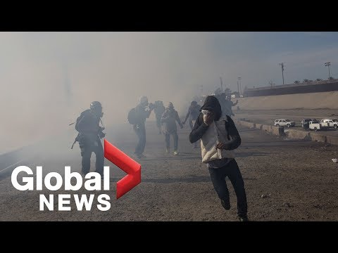 Migrants run from tear gas launched near U.S. border fence