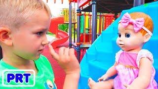 Vlad e Nikita brincam com bonecas no playground ao ar livre