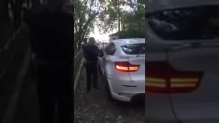 Сотрудник ДПС пытается разбить стекло BMW X6