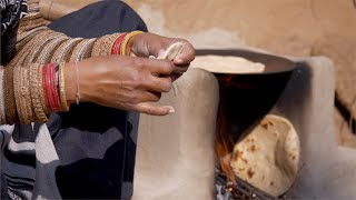Indian woman making roti in chulah / mud firewood for her family