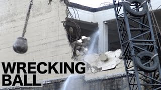 Wrecking ball in action demolishing a concrete building